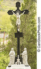 Religious cross memorial with crucified Jesus.