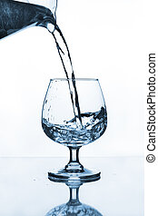 water jug pouring to wine glass on glass table