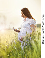 Pregnant woman praying - Outdoor portrait of young pregnant...