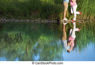 Pregnant couple by the lake - Happy young pregnant couple...
