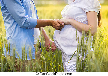 Pregnant couple praying - Outdoor portrait of unrecognizable...