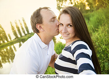 Pregnant couple taking selfie - Happy young pregnant couple...
