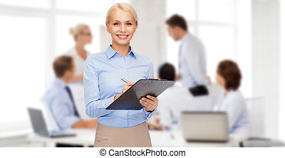 smiling businesswoman with clipboard and pen - business and...