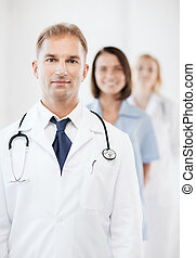 doctor with stethoscope and colleagues - healthcare and...