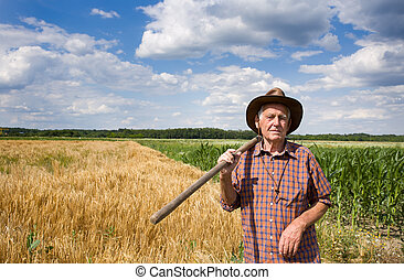 Man with fork in field - Old man farmer holding fork in...