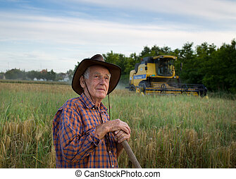 Harvesting - Proud old peasant standing on field with...