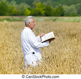 Agronomist in field - Old agronomist in white coat examining...
