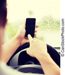man using phone while driving the car