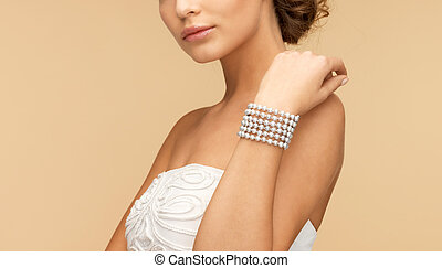 woman with pearl bracelet - beautiful bride wearing pearl...