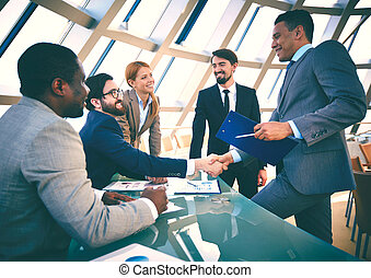 Business agreement - Group of business people looking at...
