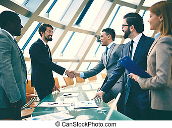 Joint business - Group of business people looking at their...