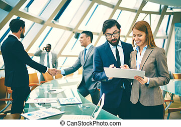 Business life - Two business people discussing data or...