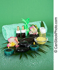 Salt, oil, stones, candles and a towel on a green background
