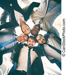 Companionship - Group of friendly businesspeople in suits...