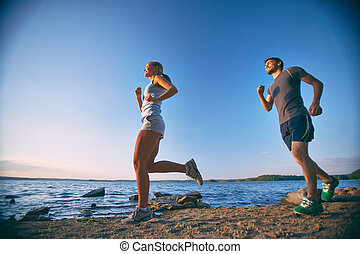Running along coastline - Photo of happy young dates running...