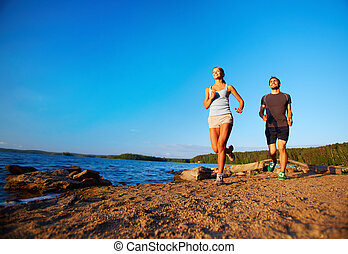 Morning recreation - Photo of young couple running along...