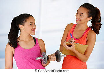 Personal Training - Woman working out while at the gym with...