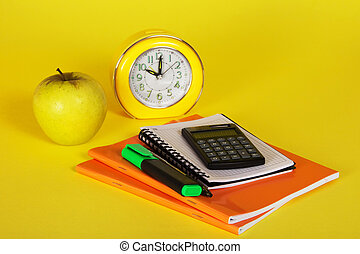 Exercise books, a notepad, calculator and apple