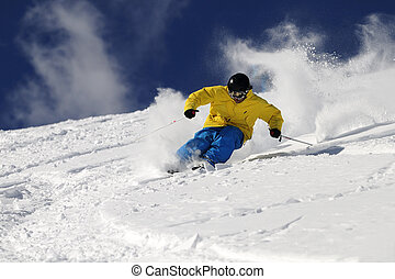 Freeride Skier - Freeride skier in powder snow against blue...