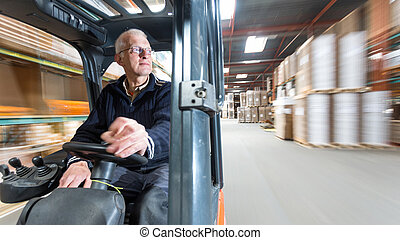 Forklift ride - Elderly man driving a forklift trough a...