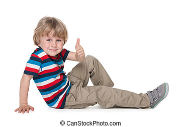 Little boy on the floor holds his thumb up