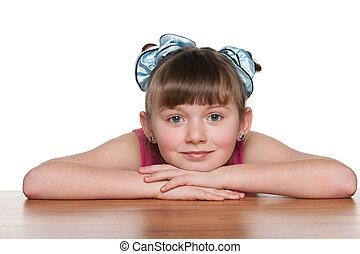 Pensive little girl at the desk