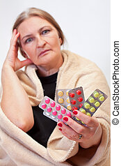 Lets be well - Beautiful aged woman taking pills to be well