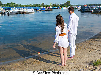 Man and woman standing on the river bank and see off toy...