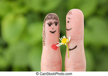 Happy couple. Man is giving flowers to a woman. Finger...