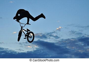 BMX rider making a bike jump - Silhouette of a BMX rider...