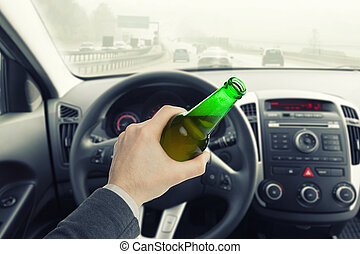 Male holding bottle of beer while driving car - Male with...