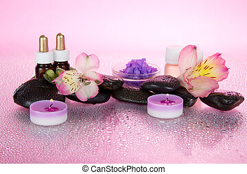 Spa set of aromatic oils, stones and candle on pink...