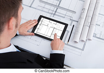 Architect Using Digital Tablet On Blueprint In Office - High...