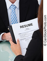 Female Candidate Holding Resume At Desk - Cropped image of...