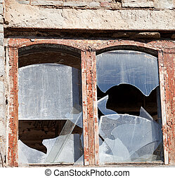 Wooden wall of old destroyed house with broken windows