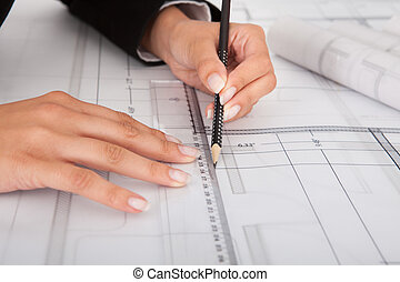 Cropped Image Of Businesswoman Working On Blueprint -...