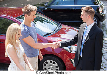 Salesman And Couple Shaking Hands By Car - Young salesman...