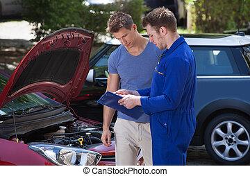 Mechanic Showing Clipboard To Customer By Breakdown Car -...