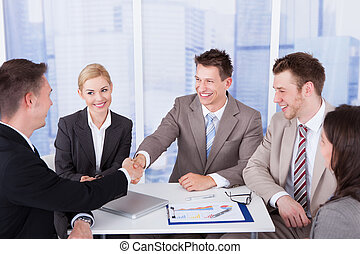 Businessmen Shaking Hands In Front Of Colleagues - Two...