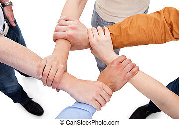 Friends Linking Hands In Team - Cropped image of young...