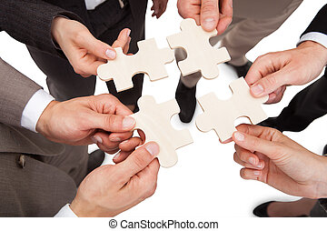 Business People Fixing Jigsaw Pieces - High angle view of...