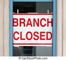 Branch Closed - A sign in a store window reading Branch...