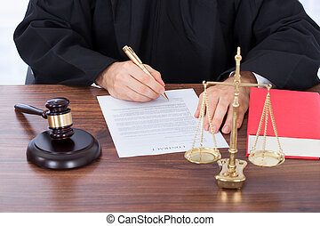 Judge Signing Contract Paper At Desk - Midsection of male...