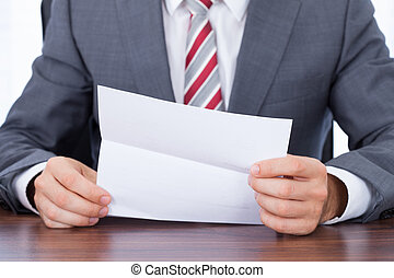 Businessman Reading Document At Desk - Midsection of...