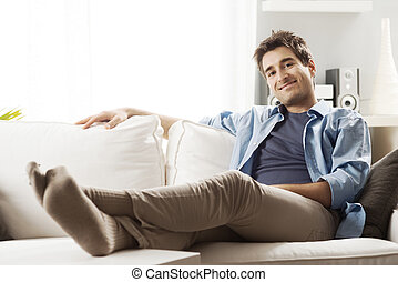 Young man relaxing on sofa in the living room smiling at...