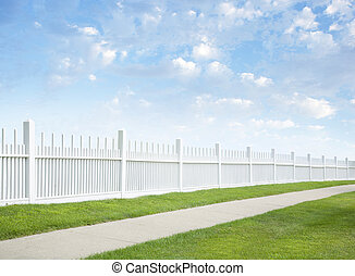 White fence, grass, sidewalk, blue sky and clouds - A white...