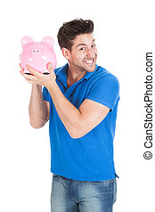 Young Man Holding Piggybank - Portrait of young man holding...