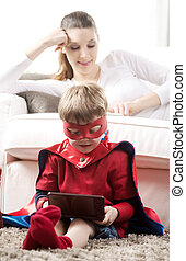 Playing videogames - Cute superhero boy playing videogames...