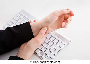 Businesswoman Suffering From Wrist Pain - Cropped image of...