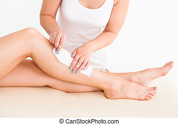 Female Therapist Waxing Customer's Leg - Midsection of...